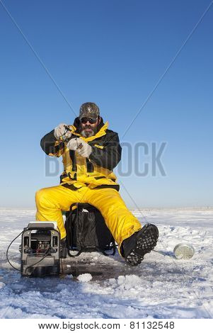 Ice fisher man with beard fighting a fish.