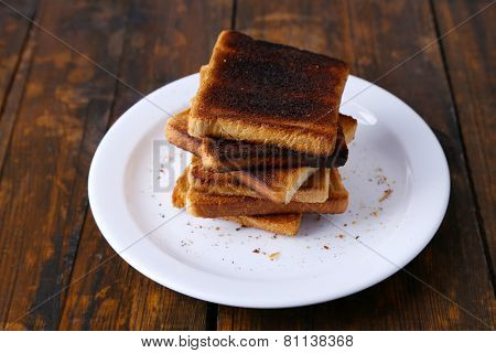 Burnt toast bread on plate, on wooden table background