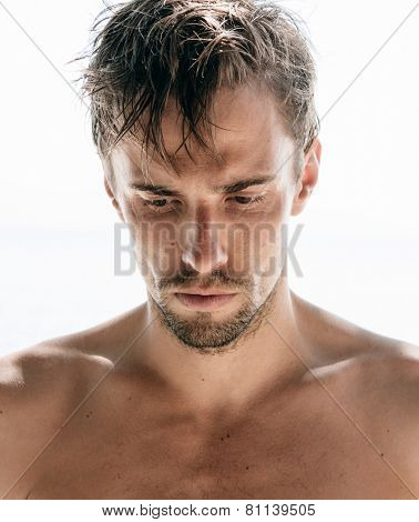 Serious shirtless attractive young man with a goatee staring thoughtfully at the ground, close up head and shoulders isolated on white