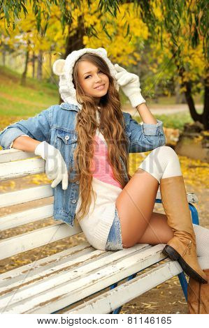 Happy young woman dressed in a white bear hat resting in autumn park.