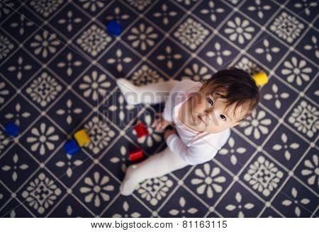 Little baby girl playing with toys