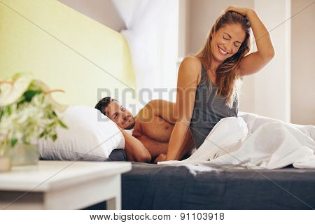 Happy young couple waking up in the morning on bed. Young man and woman smiling feeling relaxed in morning. poster