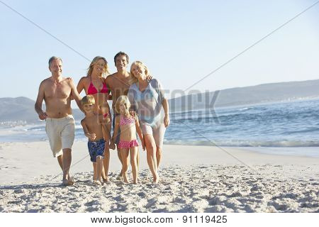 Extended Family Walking Along Sandy Beach By Sea