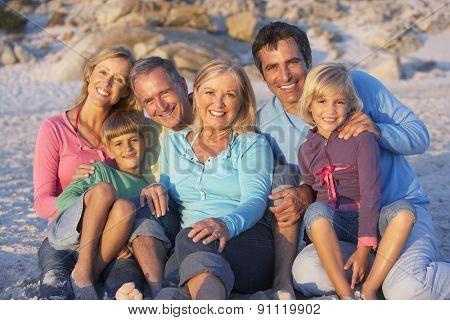 Three Generation Family On Holiday Sitting On Beach