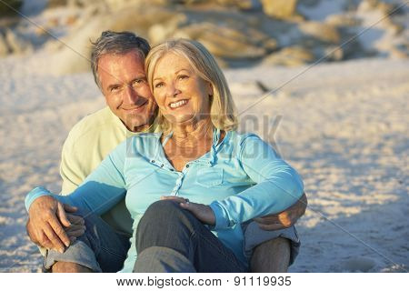 Senior Couple On Holiday Sitting On Sandy Beach