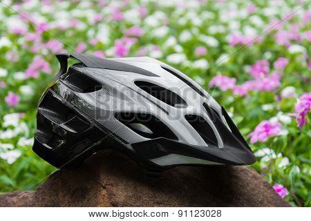 Mountain bike helmet on a rock with purple flower background