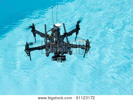 Flying black drone with camera above water poster