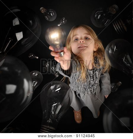 Child Holding Bright Light Bulb On Black Background