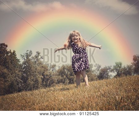 Happy Child In Nature Field With Rainbow