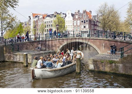 Open Boat Full Of Young People Under Bridge In Amsterdam Canal On Sunny Spring Day