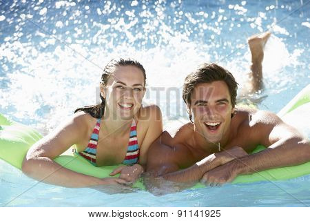 Young Couple Having Fun With Inflatable Airbed Swimming Pool Together