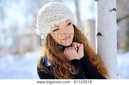 Beautiful Brunette In A White Hat Standing Near Birch In Winter