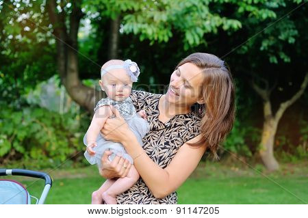 Smiling Mother And Baby Playing In Park