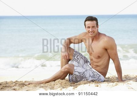 Young Man Wearing Swimming Costume Sitting On Beach
