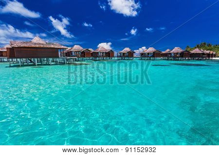 Luxurious overwater bungallows in blue lagoon on a tropical island of Maldives poster