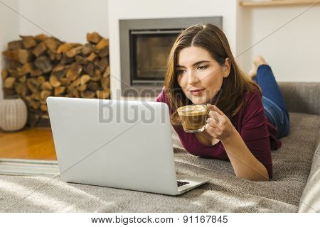 Beautiful woman at home working while drinking one capuchino