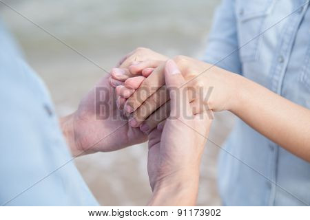 couple holding hand by the sea