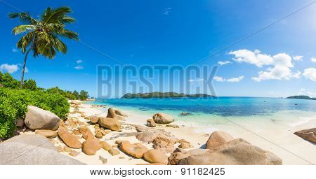 Beautiful beach Anse Takamaka seen from the granite boulders, La Digue island, Seychelles. Panorama