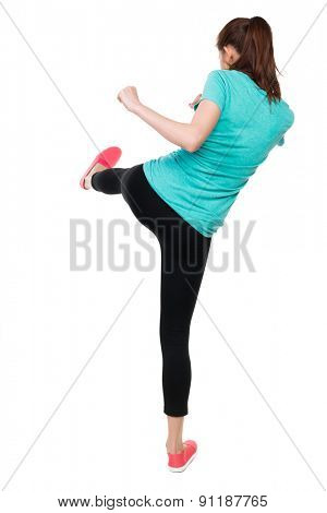 skinny woman funny fights waving his arms and legs. Rear view people collection.  backside view of person.  Isolated over white background. Sportswoman swung his left foot.