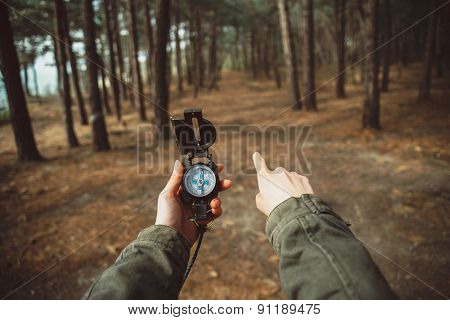Hiker With Compass Pointing Direction In The Forest