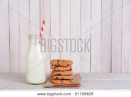 An after school snack of cookies and milk on a rustic wood set. A small bottle of milk with a drinking straw and a stack of chocolate chip cookies. Horizontal format with copy space.