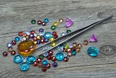 Jewelry tweezers and multicolored gems on a wooden background. poster