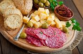 Antipasto catering platter with salami and cheese on a wooden background poster
