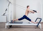 Pilates reformer workout exercises man at gym indoor poster