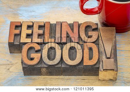 feeling good - words in vintage letterpress wood type printing blocks stained by color inks with a cup of coffee