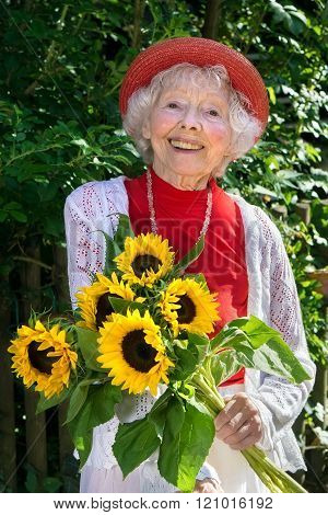 Friendly Senior Lady With A Bunch Of Sunflowers.