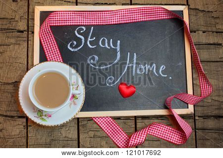 Chalkboard with the words STAY HOME handwritten in chalk next to a cup of tea on a rough wooden background