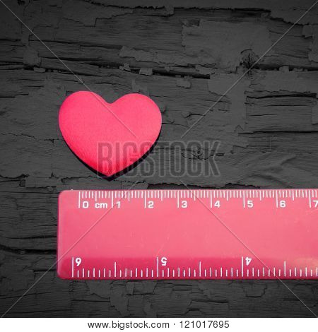 Red love heart next to a red measuring ruler - conceptual image, how big is your heart