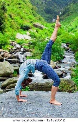 Woman doing yoga asana eka pada urdva dhanurasana Upward Bow Pose outdoors at waterfall in Himalayas