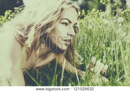 beautiful blond girl on green field with flowers