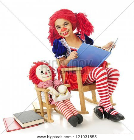 A young living rag doll in a rocking chair happily reading to her own rag doll, also in a rocking chair.  On a white background.