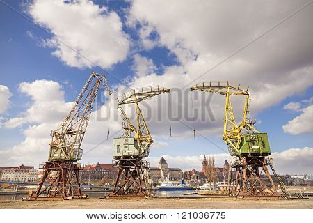 Three Old Cranes Standing By The Odra River In Szczecin, City Landmarks In Distance, Poland
