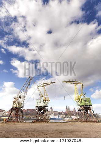 Three old cranes standing by the Odra River in Szczecin.