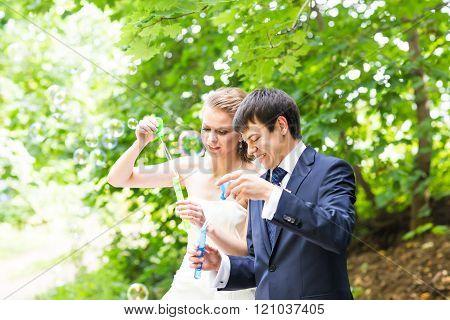 beautiful wedding couple blowing bubbles
