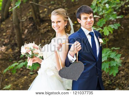 bride and groom holding a heart shaped  sign.