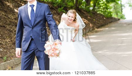 Just married couple running on a park