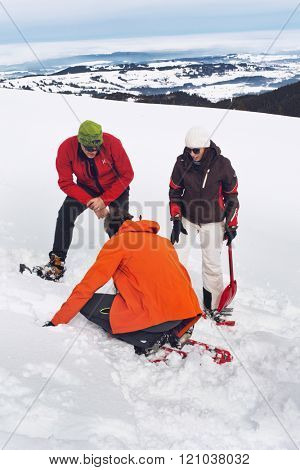 WERTACHER HOERNLE, WERTACH, GERMANY - FEBUARY 28 2016: Team of three rescuers searching for a lost shepherd in deep fresh winter snow on a mountain in a search and rescue or retrieval expedition