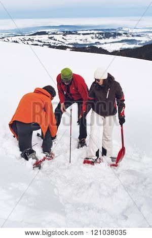 WERTACHER HOERNLE, WERTACH, GERMANY - FEBUARY 28 2016: Three rescuers training in a search and rescue operation locating a lost shepherd using a GPS signal on a snowy alpine mountain peak