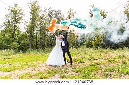 Wedding couple with color smoke in the summer park.