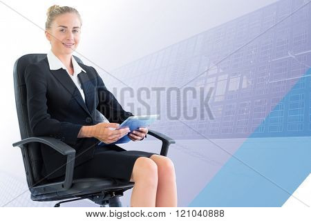 Businesswoman sitting on swivel chair with tablet against skyscraper