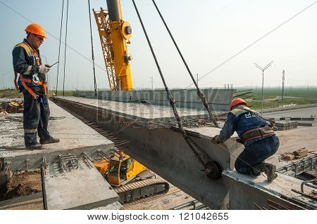 Two workers mouning bridge span