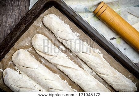 Four baguettes before baking on a wooden table