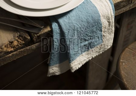 Blue Dinner Napkin Dangling From Edge Of Wooden Table