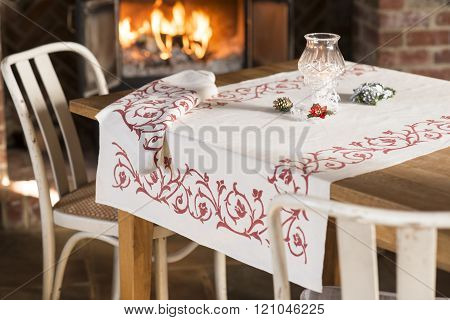 Tablecloth With Red Floral Design On Table Near Blazing Fireplace