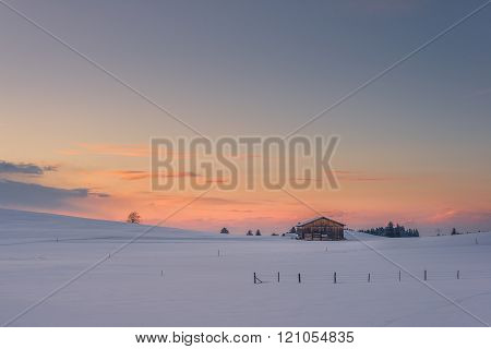 lonely chalet on snowy meadow at winter sunset and orange clouds