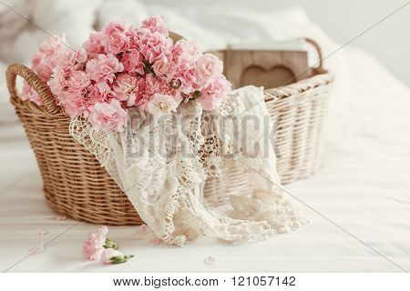 Shabby chic style. Pink pastel flowers in wicker basket on the bed.